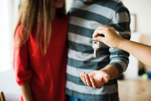 A Young Couple Holding the Key to Their New Home